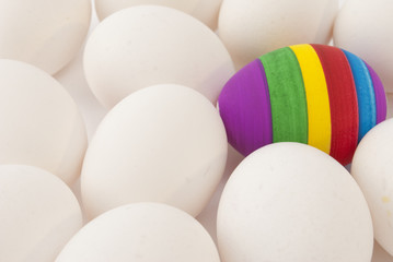One painted easter egg among white ones
