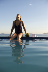 Woman relaxing on a swimming pool with a sea view