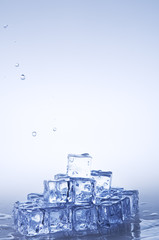 Mineral water drops falling on  frozen crystal transparent ice c