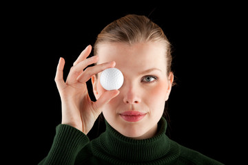 woman in a green turtleneck holds one golf ball in front of her