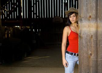 Cowgirl in barn doorway