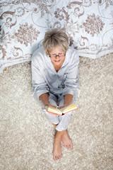 Seniorin liest ein Buch im schlafzimmer