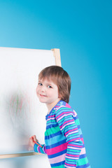 Little girl with pencil at easel