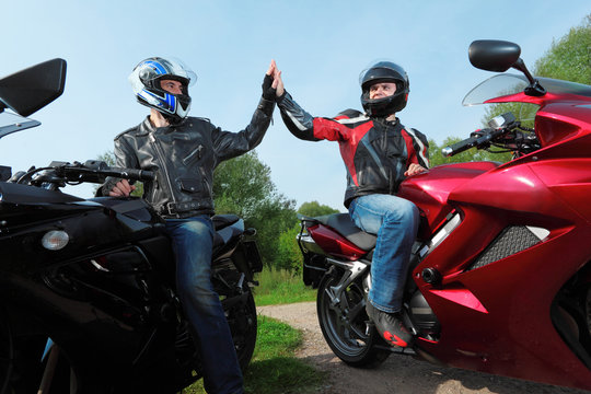 two motorcyclists greetings on country road
