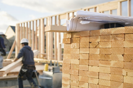 Stacked Lumber and Blueprints at a Construction Site