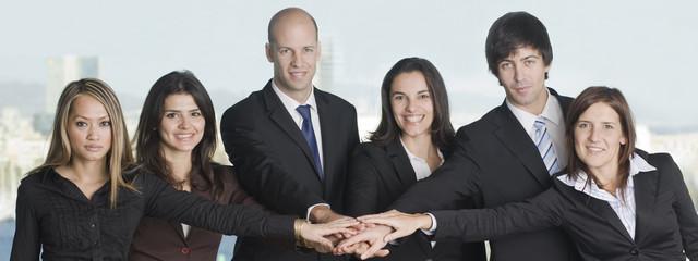 Sechs Geschäftsleute legen die Hand auf gute Zusammenarbeit
