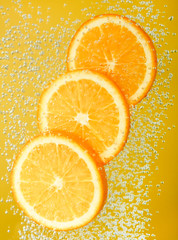Fresh orange dropped into water with bubbles.