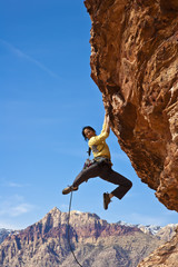 Female rock climber reaching for the summit.