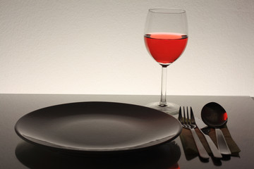 red wine and glass plate fork spoon and knife