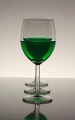 three wine glasses in a row with green wine