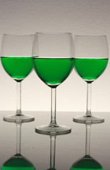 three win glasses with green wine
