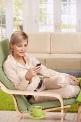 Woman using cellphone in armchair