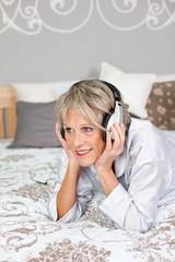 moderne seniorin mit hört musik im bett