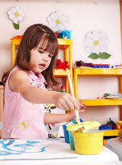 Child preschooler with picture and brush in play room.