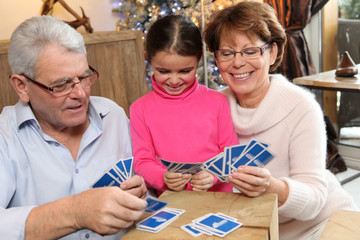 Fillette jouant aux cartes avec ses grands-parents