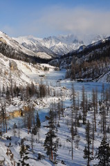 River under ice in the  winter snowy mountain