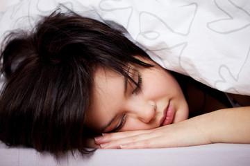 junge frau schläft unter der bettdecke