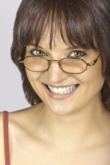 Junge Frau blickt über die Brille