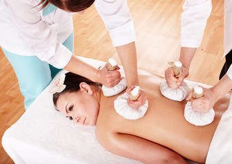 Girl  having Thai herb compress massage in beauty spa.