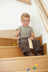 Little boy playing on stairs