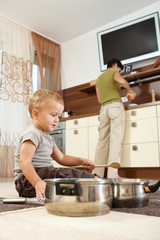 Little boy playing with cooking pots