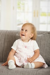 Happy babaygirl sitting on sofa