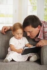 Father and toddler reading book on sofa