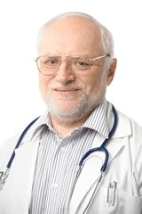 Portrait of senior doctor looking at camera
