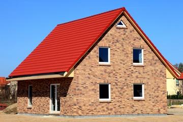 Neubau Einfamilienhaus neutral vor blauem Himmel