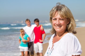 senior woman with family on beach