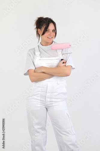 Femme peintre en b timent avec un rouleau de peinture la main photo libre de droits sur la for Peintre en batiment
