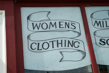 Womens clothing sign in window.