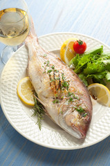 grilled red snapper with salad and glass of wine
