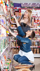 Two woman choose food in supermarket