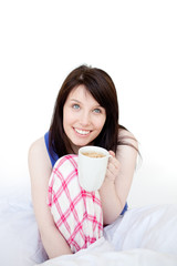 Mirthful woman drinking coffee sitting on bed