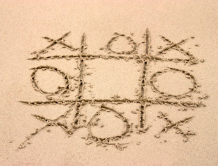 Tic tac toe game drawn in the sand on the beach