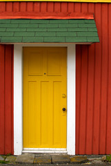 Yellow door in a red wall under a green awning