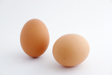 Two eggs with white background, one standing.