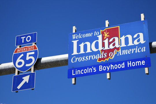 Welcome to Indiana road sign against blue sky.