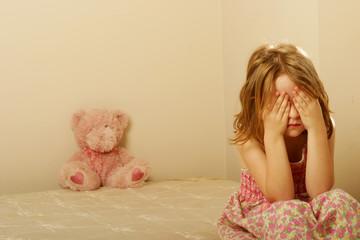 Sad girl sitting on an old mattress
