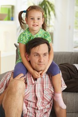 Little girl on father's shoulders