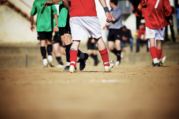 Soccer players on a sand field
