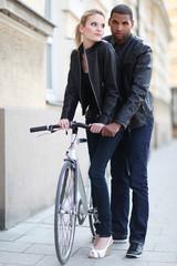 Paar in Lederjacke mit Fahrrad