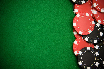 Black and red gambling chips on green felt background