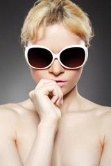 Fashion woman with sunglasses on gray background