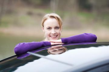 junge frau lehnt auf autodach