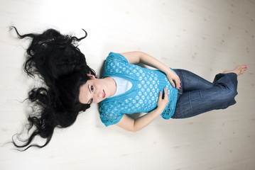 Beautiful woman with long hair lying on floor