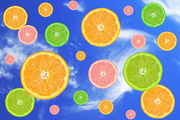 citrus fruits slices, falling in a blue sky