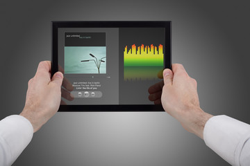 hands holding a touchpad pc, using the music programme