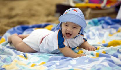 Cute baby boy on a beach towel